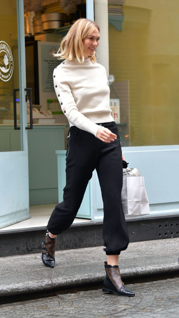 Karlie Kloss in a pretty white sweater, black capris, gold hoop earrings, and Louis Vuitton shoes at Stoney Clove Bakery in Paris