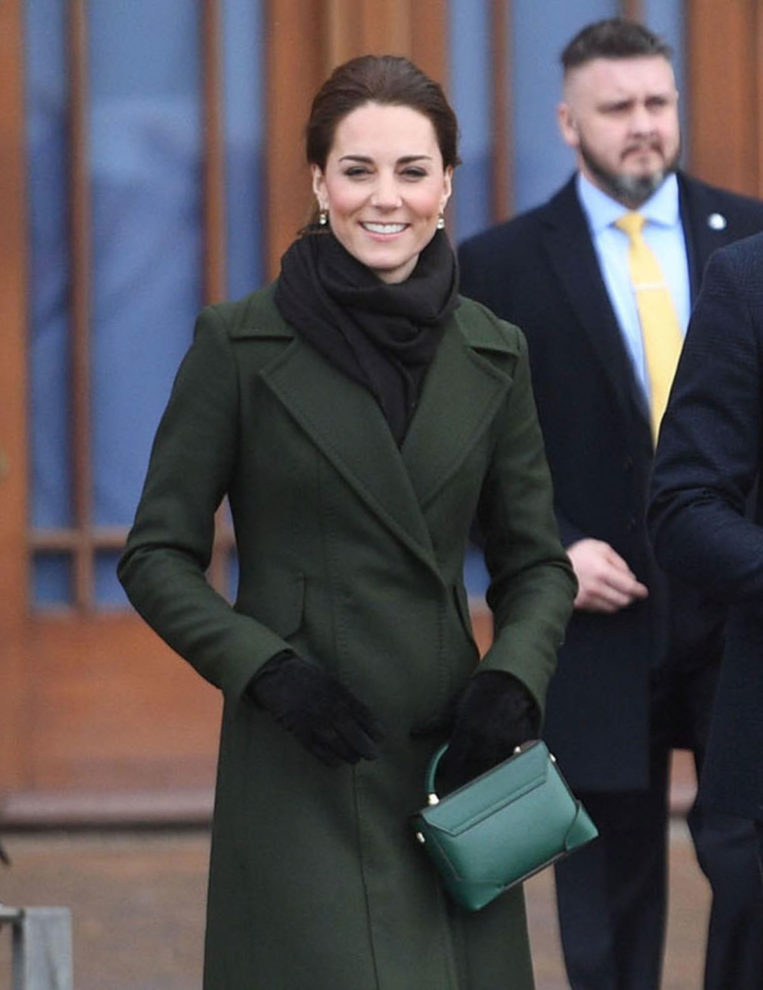 Kate Middleton in a wore an olive Sportsmax coat, a recycled green Manu Atelier bag, and black knee-high boots at Blackpool Tower